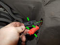 Pull the electrical connectors for the harness out and pry open the two tabs on each connector (green arrows).