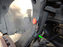 Pull the remainder of the wiring harness through the hole in the upper control arm (green arrow).