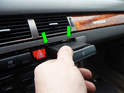 Press the two retaining clips on the dashboard (green arrows) up and pull the cupholder assembly out.