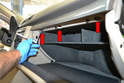 First open the glove box and remove the three 8mm screws along the upper ledge of the glove box (red arrows).