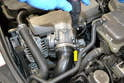 Begin by using a flathead screwdriver and removing the clamp holding the intake hose to the throttle body (yellow arrow).