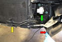 Slide the air diverter for the intercooler away from the front of the car (red arrow) and use a T20 Torx and first remove the single screw holding the line in front of the condenser in place (yellow arrow) and then use a T30 Torx and remove the single screw holding the line in the front (green arrow).
