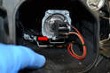 With the cover open reach in and release the wire clip (red arrow) that holds the bulb in the reflector.