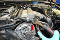Since you have already drained the coolant, use a set of pliers and remove the coolant hose from above the battery to give you more room to work (red arrow).