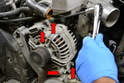 Use a 6mm Allen and remove the four bolts holding the alternator in place (red arrows).