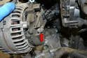Use a 13mm wrench and remove the main strap (red arrow).