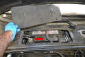 Begin by removing the panel for the battery and disconnecting the ground terminal (red arrow).