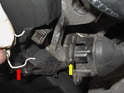 On the front of the engine, remove the wiring harness for the camshaft positioning sensor by unclipping the wire (red arrow) and slipping the connection off (yellow arrow).