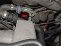 Using a set of pliers, remove the larger vacuum line from the rear of the intake manifold (red arrow).