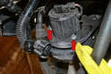 Use a 10mm socket and remove the three 10mm bolts holding the pump in place (red arrows, two shown).