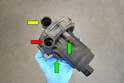 With the pump removed from the vehicle, you can see the inlet opening (yellow arrow), pressure opening (red arrow) and the rubber isolating bolts (green arrows).