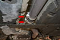 Working below the vehicle, remove the two 17mm nuts holding the connecter to the cat pipe and exhaust pipe (red arrows).