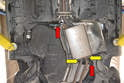 The primary muffler is held in place by two hangers attached to rubber isolating mounts (red arrows).