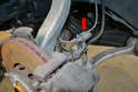 Begin by disconnecting the brake pad wear sensor from the harness (red arrow).