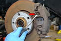 Place a large flathead screwdriver between the caliper and retaining clip (red arrow).