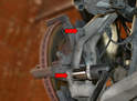 Use a 21mm socket and breaker bar to remove the two 21mm bolts holding the caliper mounting bracket to the wheel bearing housing (red arrows).
