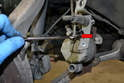 Remove the brake hard line from the caliper using an 11mm flared nut wrench (red arrow).