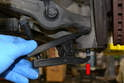 Use a ball joint separator to separate the link from the housing (red arrow).