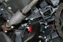 The booster rod sits in a plastic clip in the brake pedal (red arrow).
