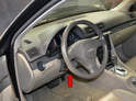 Using the steering column adjustment (red arrow), pull the steering wheel away from the dash and lower it as far is it will go.