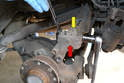 Track Control Arm- Use an 18mm socket and wrench and remove the single nut and bolt that connect the upper section of the wheel bearing housing (red arrow) to the track control arm (yellow arrow).