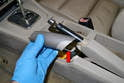 With the handle off you can better see the small metal tab you are trying to unhook from the handle shaft (red arrow).
