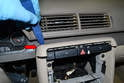 Use a trim removal tool and gently pry the upper center trim piece away from the console (red arrow).