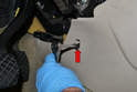 Remove the trim pieces and using an 8mm socket remove the forward foot well bolt (red arrow, one on each side).