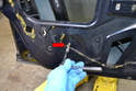 Remove the T25 screw holding the rear window regulator arm to the bottom inner door skin (red arrow).
