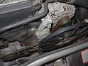 This general image of the front of the engine compartment, with the radiator support panel moved forward into the service position, gives an overview of the air conditioning compressor belt and shows the portion of the serpentine belt that turns the alternator.