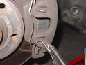 Use some pliers to grip the one-piece spring clip that spans the caliper.