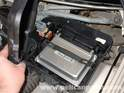 Use a flat screwdriver to pry away the metal clip holding the ECU in place.
