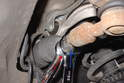 Hold the inner tie rod with a 19mm open-end wrench (red arrow) and loosen the jam nut with a 22mm wrench (blue arrow).