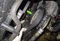 Locate the accessory drive belt tensioner and remove the dust cap (green arrow) using a flat head screwdriver.