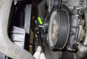 Accessory belt tensioner: Working below the thermostat, remove the 13mm tensioner mounting fastener (green arrow).