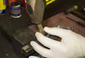 Accessory belt tensioner: Using a brass punch, drive the needle bearings out of the tensioner.