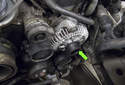 The alternator is located at the left side of the engine (green arrow).