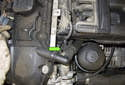 Working at the intake VANOS solenoid, disconnect the VANOS solenoid electrical connector by releasing the wire (green arrow) and pulling it off.
