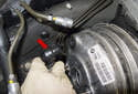 Working at the brake booster, remove the brake booster vacuum hose (red arrow) by pulling it straight out of the brake booster.