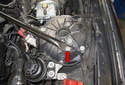 Working at the left strut tower, remove the T45 Torx fastener (red arrow).