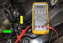 Testing with sensor removed: In this photo the wrench (green arrow) is close to the sensor (yellow arrow), so the DVOM reads 0 volts.
