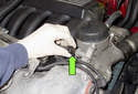 Working at the oil filter housing, disconnect the oil pressure sensor by pressing the retaining spring and pulling it off (green arrow).