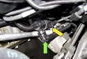 Working below the throttle body, disconnect the purge solenoid electrical connector (yellow arrow) and remove the hose (green arrow).