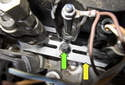 Turbocharged engines: Working at the base of the fuel injector, remove the E10 fastener (green arrow) from the retainer.