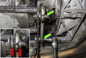 Working at the transmission cross member, remove the E10 bolts while counter-holding the 13mm nuts (green arrows).