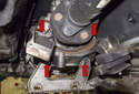 Working at the rear of the transmission, remove the four E12 bracket fasteners (red arrows).