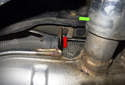 Then remove the rear most hanger fastener (red arrow), a 13mm nut located to the left side of the tail pipe (green arrow).