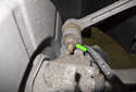 Working at the traction strut on the brake rotor side, remove the 16mm nut (green arrow).