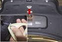 Start by removing the emergency trunk release handle from the trunk lid (red arrow).