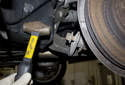 Then lightly tap it using a soft-faced hammer to begin to move the bolt out of the control arm.